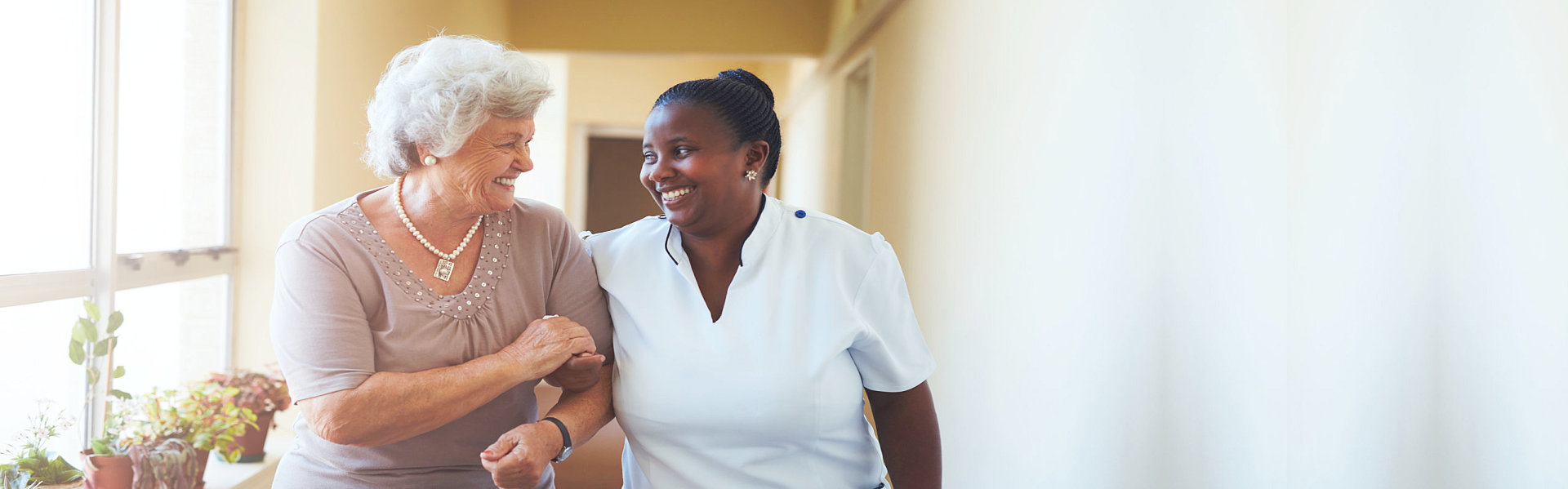 portrait of smiling caregiver and senior walking together
